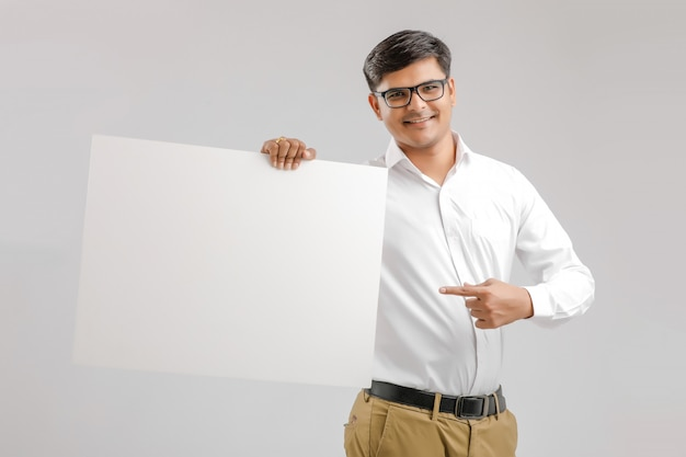 Happy young indian man showing blank board