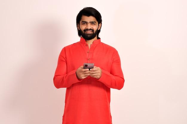 스마트폰을 사용하고 sms 또는 문자 메시지를 보내는 kurta를 입은 행복한 젊은 인도 남자