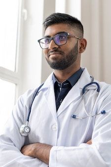 Счастливый молодой индийский студент-медик носит очки и стетоскоп на портрете в белом халате в