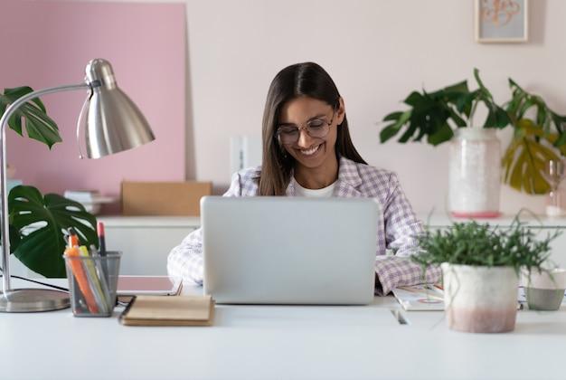 사무실 책상에 앉아 인터넷에서 일하는 화면을 보는 컴퓨터를 사용하는 행복한 젊은 인도 혼혈 여성