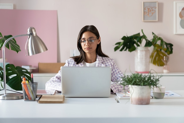 Happy young indian mixed-race business woman using computer looking at screen working in internet sit at office desk