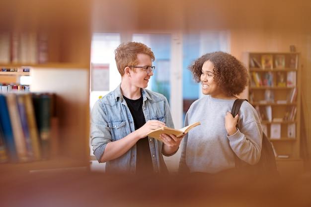 図書館での物語の本からの物語の詳細を議論する幸せな若い異文化カップル
