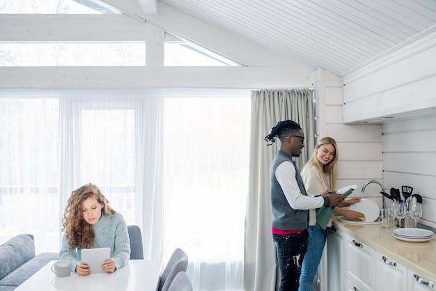Счастливая молодая межкультурная пара моет посуду у раковины на кухне, пока их друг использует мобильный гаджет за столом