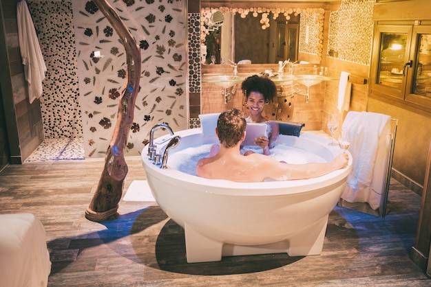Happy young interracial couple relaxed enjoying their self in the jacuzzi drinking wine and with a tablet