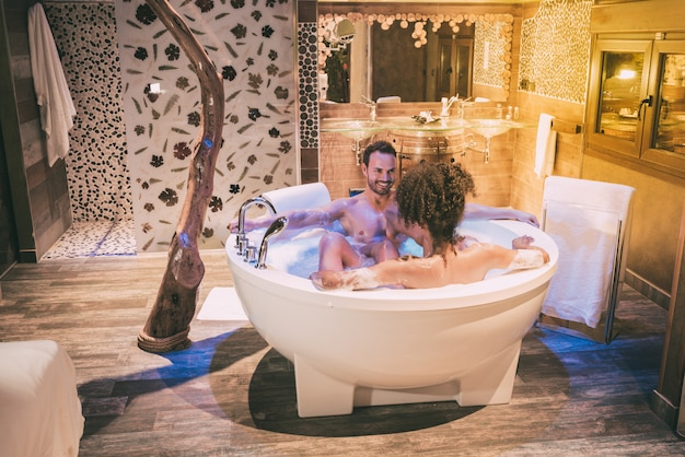 Happy young interracial couple relaxed enjoying their self in the jacuzzi