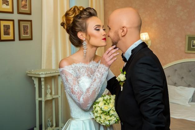 幸せな若いちょうど結婚したカップルが自宅でキスをしているウェディンスーツ