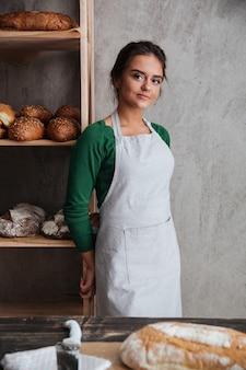 Счастливый молодой леди бейкер, стоя в пекарне возле хлеба.