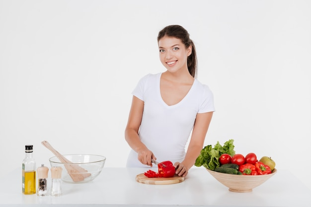 Happy young lady cooking with vegetables