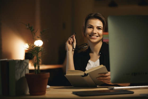 Happy young lady designer using computer and holding book