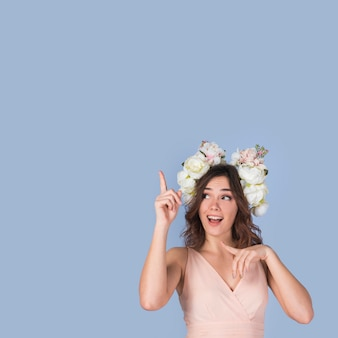 Happy young lady in dress with flower wreath pointing upstairs