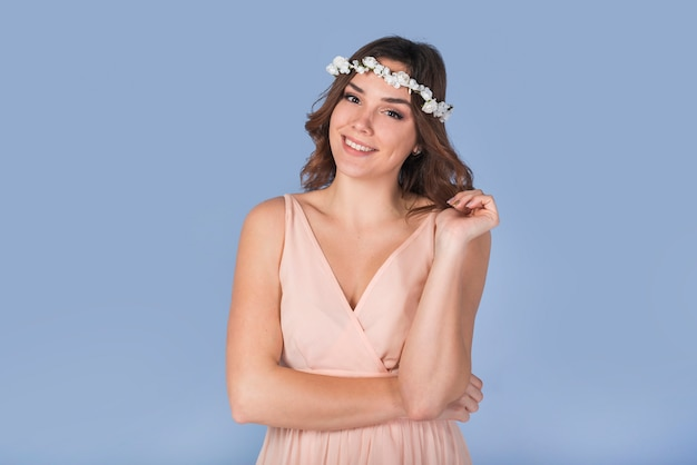 Happy young lady in dress with white wreath on head