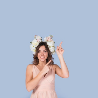 Happy young lady in dress with white wreath pointing upstairs