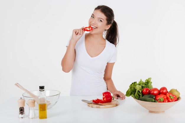Happy young lady dressed in white t-shirt cooking with vegetables while eating them