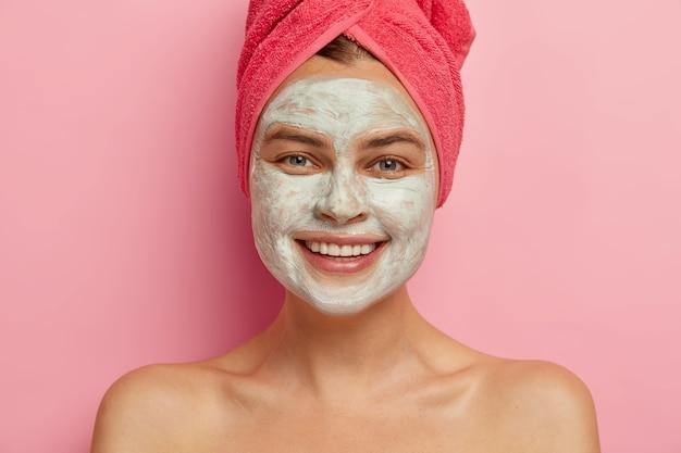 La giovane donna felice riceve una maschera di bellezza sul suo bel viso per morbidezza, sorride ampiamente, sta in topless al coperto, si preoccupa della salute e dell'aspetto, l'asciugamano avvolto sulla testa, esprime emozioni positive.