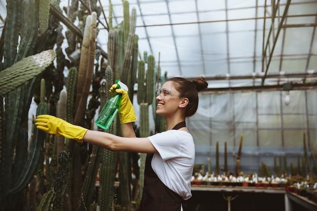 Giovane signora felice in vetri che stanno nella serra vicino alle piante.