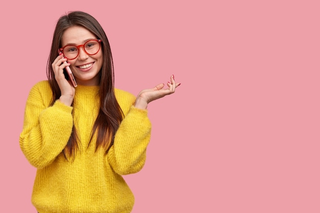 Happy young lady has telephone conversation with best friend, gestures actively as tells what happened with her during day