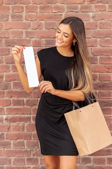Happy young lady holding receipt mock-up