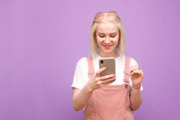스마트 폰을 사용하고 웃는 귀여운 옷에 행복 젊은 아가씨