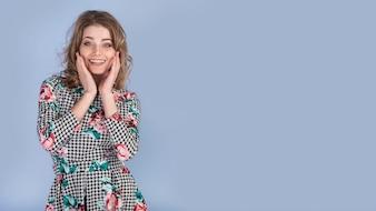 Счастливая молодая леди в элегантном платье с руками на лице