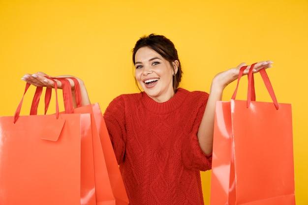 노란색 스튜디오에서 쇼핑 가방과 함께 빨간 스웨터에 행복 한 젊은 아가씨.