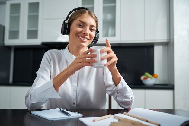 Счастливая молодая леди в беспроводных наушниках сидит за кухонным столом и пьет горячий чай