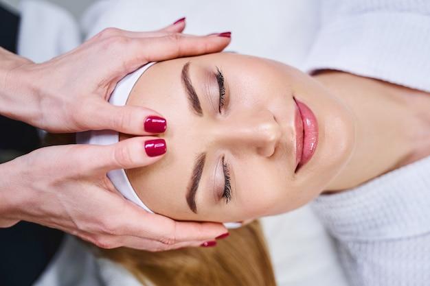 美容師が手で額のマッサージをしている間、幸せな若い女性はリラックスしています