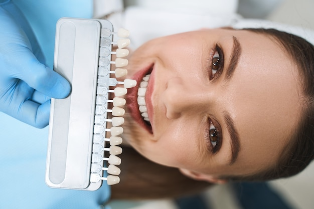 Happy young lady is visiting dental clinic for taking care of teeth and getting better smile