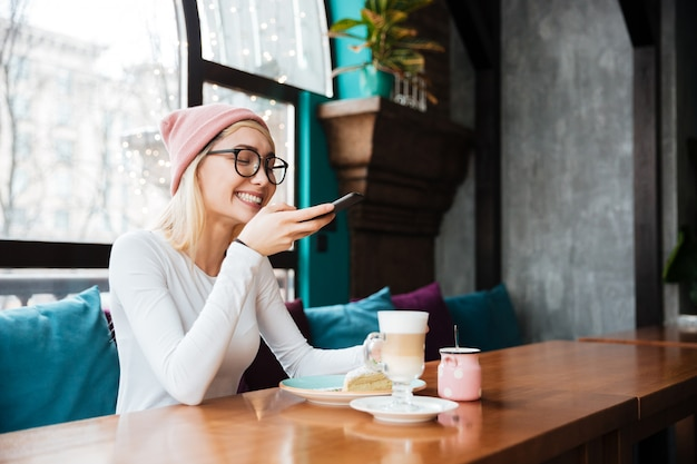 Happy young lady make photo of cake and coffee