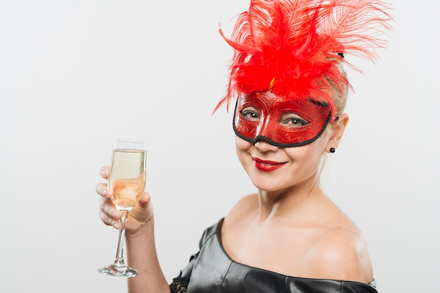 Happy young lady in mask with red feathers holding glass