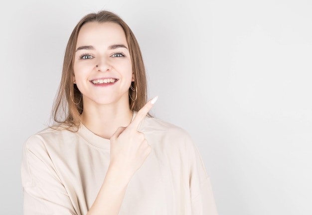 Happy young lady pointing at copy space