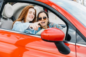 Happy young lady pointing to cheerful woman and sitting in car