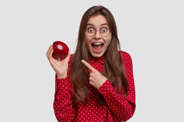 La giovane donna felice indica la mela rossa succosa, dimostra cibo sano, si tiene a dieta, mantiene la mascella aperta, ha i capelli lunghi, l'espressione del viso stupita