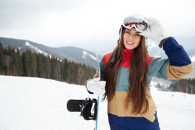 Happy young lady snowboarder on the slopes frosty winter day