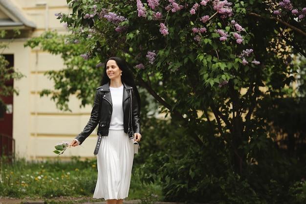 夏の日に咲くライラックの木の近くの通りを歩く幸せな若い女性