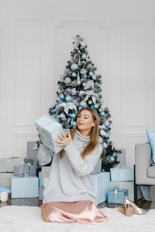 Счастливая барышня с подарками возле елки. новогодняя концепция.