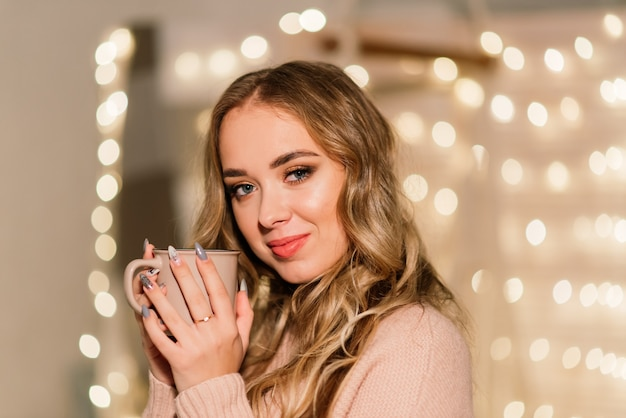 Happy young lady with long hair near the fireplace and the christmas tree, gifts. new year concept.