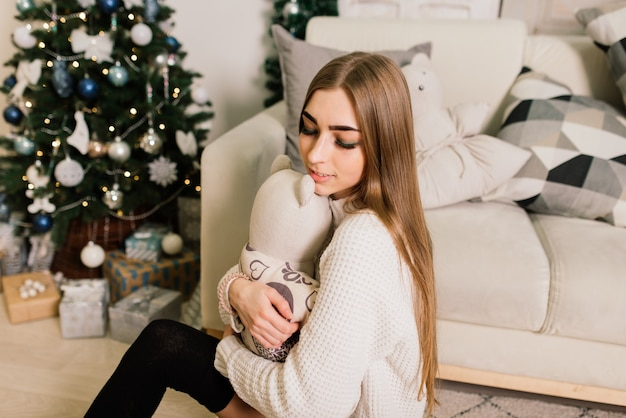 Happy young lady with long hair near the fireplace and the christmas tree,
