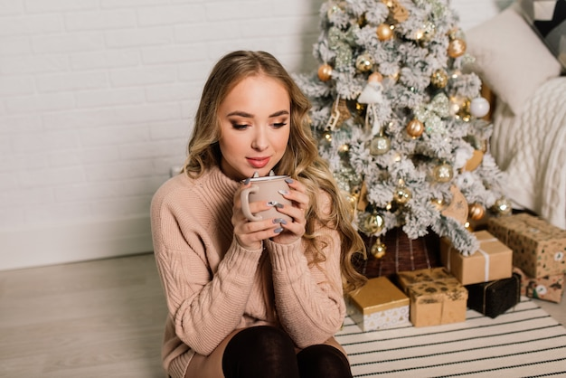 Happy young lady with long hair near the fireplace and the christmas tree