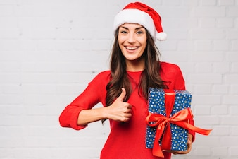 Happy young lady with present box showing good