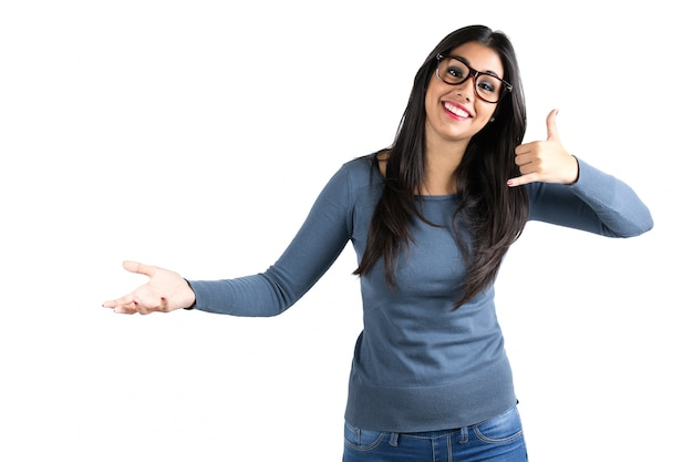 Happy young latin woman making a call me gesture
