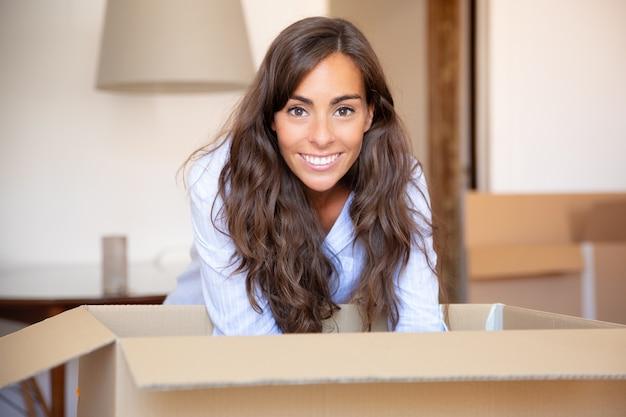 Felice giovane donna latina disimballare le cose nel suo nuovo appartamento, aprendo una scatola di cartone,