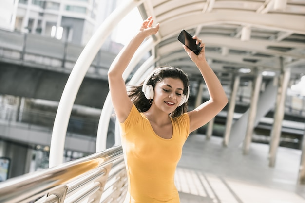 Happy young latino woman listening to music from headphones