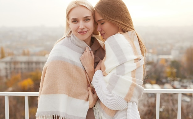 Happy young lesbian couple hugging and covering shoulders with warm plaid while standing on terrace on autumn day