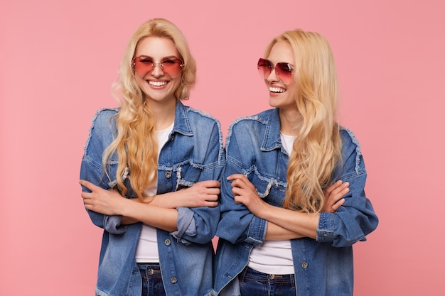 Happy young long haired blonde females dressed in sunglasses and casual clothes keeping hands folded and laughing cheerfully while posing over pink background