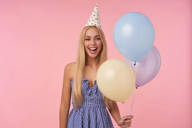 Felice giovane femmina dai capelli lunghi in posa in mongolfiere multicolori, indossando abiti estivi blu e cappello di compleanno, celebrando le vacanze, isolate su sfondo rosa