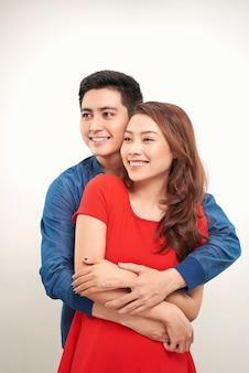 幸せな若い愛のカップルが白い背景を抱きしめて立っ