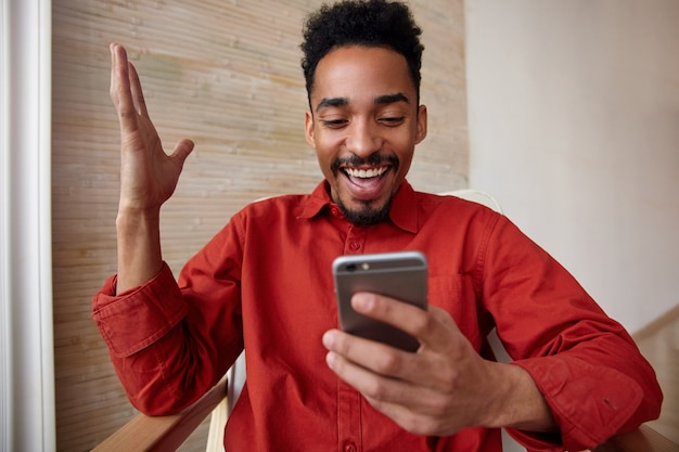 Happy young lovely bearded curly brunette male with dark skin keeping his hand raised while looking joyfully on screen of his mobile phone, posing on home interior