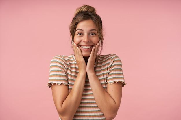 ピンクの背景で隔離、広い笑顔でカメラを元気に見ながら、上げられた手で彼女の顔を保持しているカジュアルな髪型の幸せな若い素敵なブルネットの女性