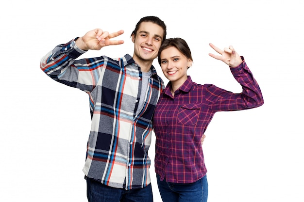 Happy young lovely couple having fun together and looking to camera over white