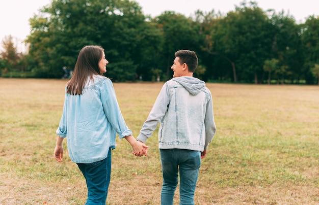 日没時に公園で屋外を歩いて一緒に時間を過ごす幸せな若い素敵なカップル